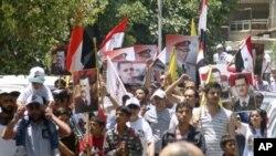這個星期敘利亞親政府的示威者在法國駐大馬士革大使館前高舉敘利亞總統阿薩德的畫像