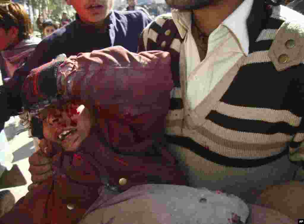 Afghans carry a wounded boy during a demonstration in Jalalabad province, February 22, 2012. (Reuters)