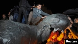 Cư dân thành phố Kharkov ở miền đông Ukraine leo lên tượng đài Lenin, cưa chân tượng rồi kéo đổ bức tượng bằng dây cáp.