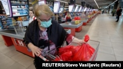 Montenegro, Podgorica, A woman wears a mask as she packs her groceries