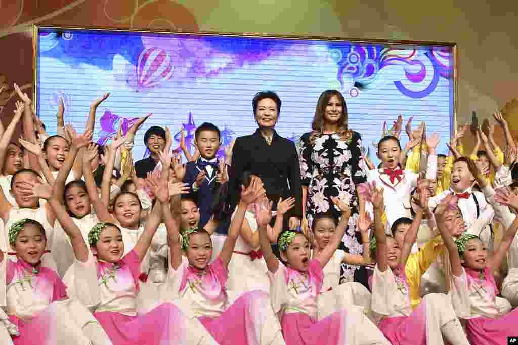 美国第一夫人梅拉尼娅·川普和中国国家主席习近平夫人彭丽媛访问北京板厂小学,观看文艺表演。孩子们围绕在她们身边欢呼(2017年11月9日)。