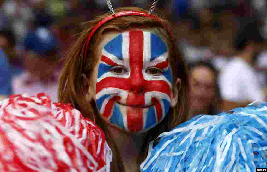 A Britain fan, with her face painted in the style of the Union Jack, smiles while attending the men's Group A football match against Senegal at the London 2012 Olympic Games in Old Trafford, Manchester, northern England July 26, 2012.