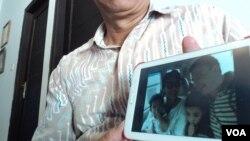 Seorang kerabat memperlihatkan foto keluarga Yuli Hastini, yang merupakan penumpang pesawat Malaysia Airlines MH17 yang jatuh di Ukraina. (VOA/Yudha Satriawan)