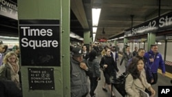 Passengers exit a subway train at New York's Times Square station, Nov. 1, 2012.