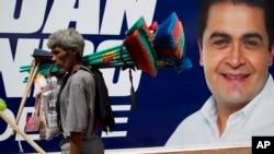 A street vendor walks past a campaign banner promoting National Party presidential candidate Juan Orlando Hernandez, in Tegucigalpa, Honduras, Nov. 23, 2013.