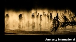 People cool down in a fountain beside Manzanares river in Madrid, Spain, June 30, 2015.