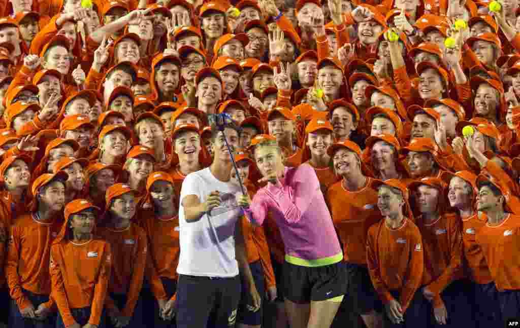 "Petenis Australia Thanasi Kokkinakis dan petenis Rusia Maria Sharapova menggunakan tongsis untuk ""selfie"" dengan para ball boy dan ball girl menjelang turnamen grand slam Australia Terbuka di Melbourne."
