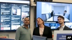FILE – Facebook's Samidh Chakrabarti, director of elections and civic engagement, from left, stands with Katie Harbath, global politics and government outreach director, and Nathaniel Gleicher, head of cybersecurity policy, in the war room in Menlo Park, Calif., Oct. 17, 2018.