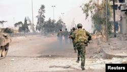 Pasukan Suriah dalam bentrokan dengan pemberontak di Aleppo (8/10). Kelompok Human Rights Watch menuduh Damaskus menggunakan bom rumpun dalam perang dengan pemberontak di Aleppo.