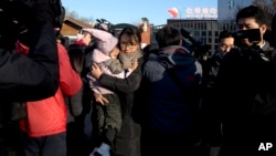 A woman leaves with a child after telling the media she came to withdraw the child from the RYB kindergarten in Beijing, China, Friday, Nov. 24, 2017. (AP Photo/Ng Han Guan)