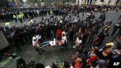 Petugas Palang Merah membawa seorang pengunjuk rasa yang terluka dalam bentrokan demonstran dengan polisi anti huru-hara saat pelantikan Presiden baru Meksiko, Enrique Pena Nieto di Meksiko, Sabtu (1/12).