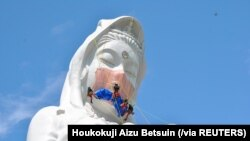 Para pekerja memasang masker pada patung Dewi Kwan Im setinggi 57 meter di kuil Houkokuji Aizu Betsuin di Prefektur Fukushima untuk berdoa agar pandemi virus corona (COVID-19) cepat berlalu, Selasa, 15 Juni 2021. (Foto: Houkokuji Aizu Betsuin via Reuters)