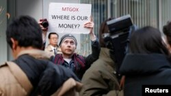 Kolin Burges, a self-styled cryptocurrency trader and former software engineer from London, holds up a placard to protest against Mt. Gox, in front of the building where the digital marketplace operator was formerly housed in Tokyo, Japan, Feb. 26, 2014.