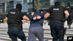 FILE - Kosovo police detain a terror suspect in the capital Pristina.