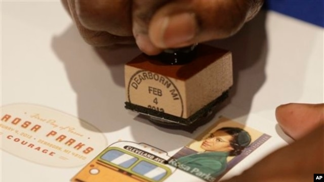 A postal service employee prepares to cancel the Rosa Parks' 100th birthday commemorative postage stamp at The Henry Ford museum in Dearborn, Mich., Monday, Feb. 4, 2013.
