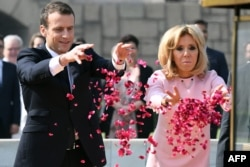 Presiden Perancis Emmanuel Macron dan istrinya Brigitte Macron menaburkan bunga di tugu peringatan Rajghat untuk menghormati Mahatma Gandhi di New Delhi, 10 Maret 2018.