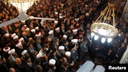 People and officials attend funeral prayers for a senior pro-Syrian government Muslim cleric Mohammed al-Buti and his grandson Ahmad al-Buti, killed in a mosque explosion on Thursday, at Umayyad Mosque in Damascus, March 23, 2013.