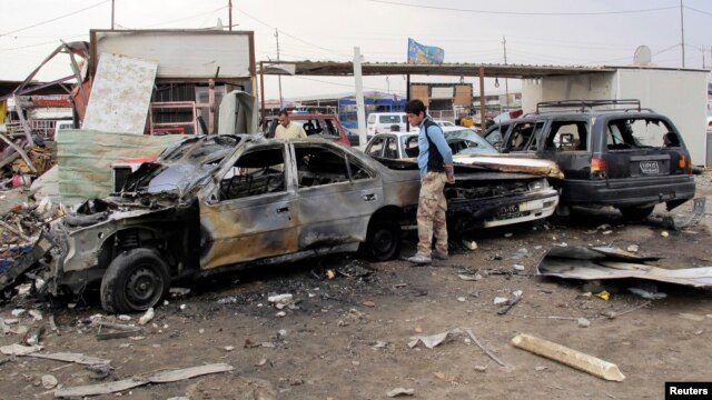 Residents gather at the site of a car bomb attack in al-Habibya district in Baghdad, April 16, 2013.