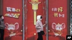 北京居民走過仍然懸掛著春節招貼畫的商場旁走過。(2020年3月8日)