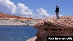 Bill Schneider berdiri di Danau Powell, 31 Juli 2021, dekat Page, Arizona. Musim panas ini, ketinggian air mencapai titik terendah bersejarah di tengah perubahan iklim di AS Barat. (Foto: AP/Rick Bowmer)