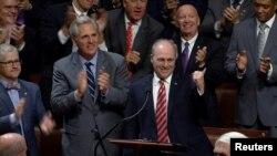 지난 6월 워싱턴 인근 야구장에서 괴한의 총격을 받았던 스티브 스컬리스 공화당 하원 원내총무(오른쪽)가 28일 석 달여 만에 의회에 복귀한 후 동료의원들의 박수를 받고 있다.