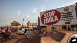 "FILE - People pass a banner reading ""STOP EBOLA"" forming part of Sierra Leone's Ebola-free campaign in Freetown, Jan. 15, 2016."