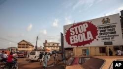 """Orang-orang melintas di depan sebuah billboard yang berbunyi """"Stop Ebola,"""" yang menjadi bagian dari sebagian kampanye bebas Ebola Sierra Leone di kota Freetown, Sierra Leone, 15 Januari 2016"""