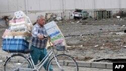 Một cư dân Sendai đi qua con đường vẫn còn đất đá đổ vỡ từ trận động đất