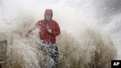 A news reporter standing near a sea wall in Cedar Key, Fla., is covered by an unexpected wave as Hurricane Hermine nears the Florida coast, Sept. 1, 2016.