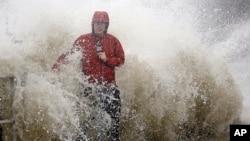 미국 남동부 플로리다주에 허리케인 '허민'이 상륙한 가운데, 1일 높은 파도가 치는 시더케이 해안에서 한 방송기자가 날씨를 전하고 있다.