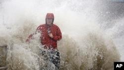 一名电视台记者在佛罗里达州喜达尔岛海边报道赫敏飓风时被大浪击中。(2016年9月1日)