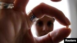 Seorang perempuan memegang pil KB di rumahnya di Nice, Perancis. (Foto: Dok)