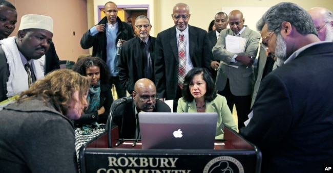 FILE - Muslim, Christian, minority and government leaders fix their eyes on a laptop screen showing a video as part of the program called Countering Violent Extremism, at Roxbury Community College in Boston, March 31, 2015.