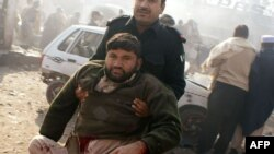 Pripadnik snaga bezbednosti pomaže ranjenima nakon eksplozija u pakistanskoj pokrajini Kajber, 10. januar 2012.