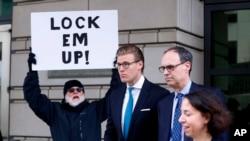 """Alex van der Zwaan, centro, a su salida de la Corte Federal del Distrito en Washington, DC tras recibir su sentencia. Un residente sostiene un cartel donde se lee """"enciérrelos""""."""