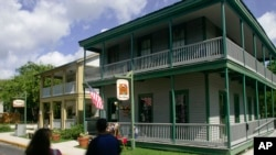 Tourists walk past The Cuna Street Toy Shop, right, and Knock on Wood, two historic buildings on Cuna Street in the historic section of St. Augustine, Florida. (file photo)