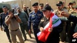 Thủ tướng Iraq Haider al-Abadi cầm quốc kỳ khi đến Mosul, Iraq, 9/7/2017.