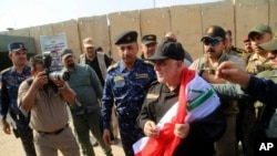 Iraq's Prime Minister Haider al-Abadi, center, holds a national flag upon his arrival to Mosul, Iraq, July 9, 2017.
