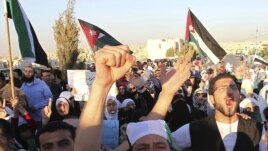 Jordanians and Syrian refugees protest the killing of at least 108 people in the Syrian town of Houla last Friday, outside the Syrian embassy in Amman, Jordan, May 30, 2012.