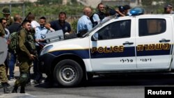 Israeli forces gather at the scene of a Palestinian car-ramming attack at the entrance of Beit Einun village, near the West Bank city of Hebron, July 18, 2017.