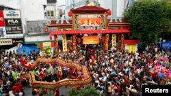 FILE - Residents watch a dragon dance ahead of the Cap Go Meh festival on Monday, which marks the end of Chinese New Year celebrations, on Malioboro street in Yogyakarta, Central Java, Indonesia, Feb. 7, 2009.