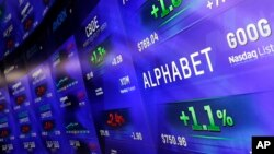 Electronic screens post prices of Alphabet stock, Feb. 1, 2016, at the Nasdaq MarketSite in New York. Alphabet, the parent company of Google, reports quarterly earnings Monday.