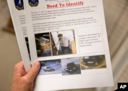 Charleston Emergency Management Director Mark Wilbert holds a flier showing surveillance footage of a suspect wanted in connection with the shooting Wednesday at Emanuel AME Church in Charleston, S.C., June 18, 2015.