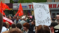 """A Russian demonstrator holds sign with caricature of Vladimir Putin and the message: """"We will throw the rat off the ship!"""" during a protest in Moscow, May 6, 2012."""