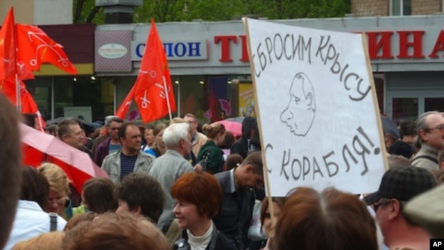 "A Russian demonstrator holds sign with caricature of Vladimir Putin and the message: ""We will throw the rat off the ship!"" during a protest in Moscow, May 6, 2012."