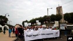 Warga Forges-les-Bains, selatan Paris, Perancis, melakukan aksi unjuk rasa, Sabtu (8/10) memprotes kedatangan migran yang sedang disebar ke seluruh negara itu sejak pemerintah menutup kamp di Calais. (AP Photo/Christophe Ena)