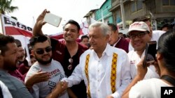 Presidential hopeful and two-time candidate Andres Manuel Lopez Obrador greets supporters as he arrives at a campaign rally for Delfina Gomez, who is running for Mexico state governor with his National Regeneration Movement, or MORENA, in Nezahualcoyotl, Mexico state, May 28, 2017.
