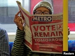 FILE - A woman reads a newspaper on the underground in London with a 'vote remain' advert for the BREXIT referendum, Britain, June 22, 2016.