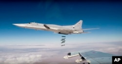 FILE - In this photo made from footage taken from the Russian Defense Ministry website on Nov. 26, 2017, Russian Tu-22M3 long-range bombers strike Islamic State targets in Syria.