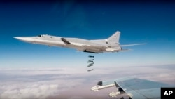 FILE - In this photo made from the footage taken from the Russian Defense Ministry official website on Nov. 26, 2017, Russian Tu-22M3 long-range bombers strike Islamic State targets in Syria.